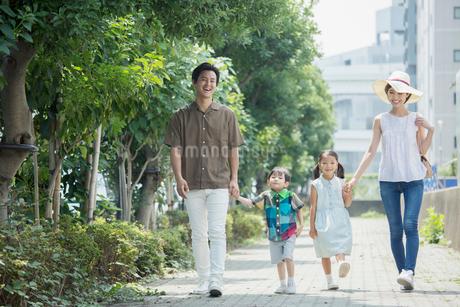 屋外を歩く笑顔の家族の写真素材 [FYI01736966]