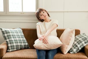 部屋のソファでくつろぐ20代女性の写真素材 [FYI01736971]