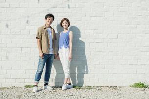 白壁の前に立つ笑顔の男女の写真素材 [FYI01736974]