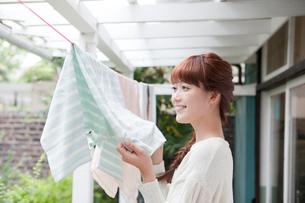 洗濯物を干す若い女性の写真素材 [FYI01736979]
