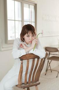 1輪の花を持ち椅子に座る20代女性の写真素材 [FYI01736990]