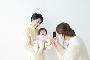 赤ちゃんをだっこする夫を携帯電話で撮る妻の写真素材 [FYI01736993]