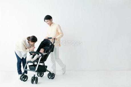 ベビーカーを押す父親と赤ちゃんをあやす母親の写真素材 [FYI01737004]
