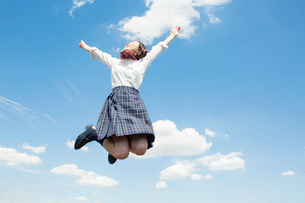 青空のもとジャンプをする女子高校生の写真素材 [FYI01737041]