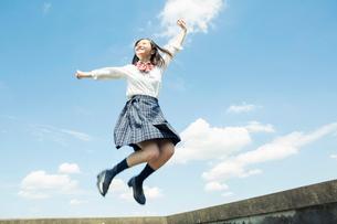 青空のもとジャンプをする女子高校生の写真素材 [FYI01737089]