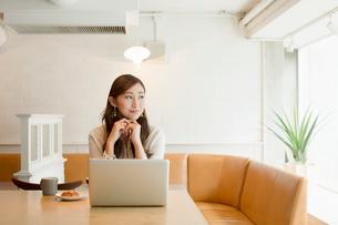 カフェでパソコンを操作する20代女性の写真素材 [FYI01737137]