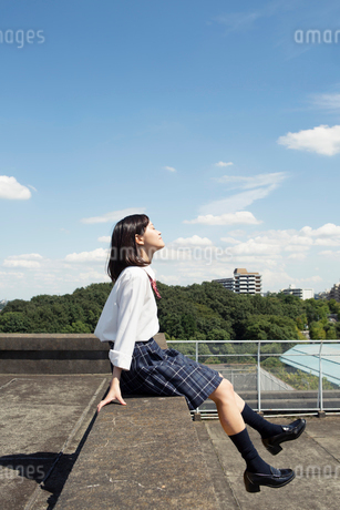 屋上に座る女子高校生の写真素材 [FYI01737169]