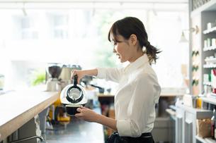 コーヒーを注ぐ20代カフェ店員の写真素材 [FYI01737174]