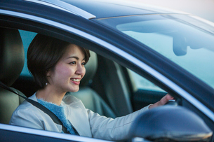 車を運転する笑顔の30代女性の写真素材 [FYI01737243]