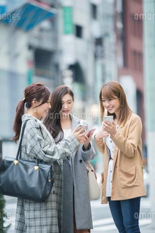街でスマホを確認する20代女性3人の写真素材 [FYI01737268]