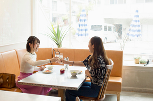 カフェでのランチタイムを楽しむ20代女性2人の写真素材 [FYI01737292]