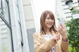街でスマホを確認する20代女性の写真素材 [FYI01737305]