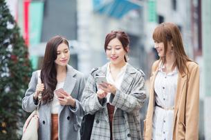 スマホを持ち街を歩く20代女性3人の写真素材 [FYI01737317]