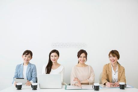 横並びに座る笑顔の20代女性4人の写真素材 [FYI01737320]