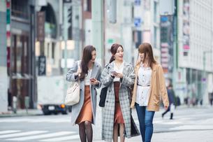 街でスマホを確認する20代女性3人の写真素材 [FYI01737373]
