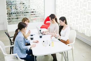 化粧品のミーティングをする20代女性4人の写真素材 [FYI01737382]