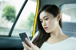 タクシー車内でスマホを操作する20代女性の写真素材 [FYI01737399]