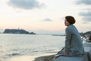 夕焼け空と海を眺める30代女性の写真素材 [FYI01737405]