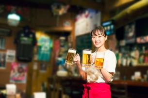 ビールを運ぶ笑顔の居酒屋店員の写真素材 [FYI01737414]