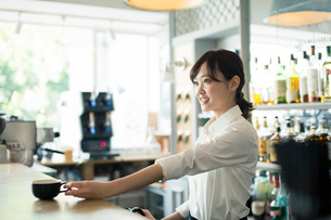 コーヒーを提供するカフェ店員の写真素材 [FYI01737428]