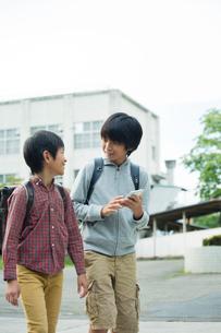 スマホを持ち会話する小学生男子2人の写真素材 [FYI01737434]