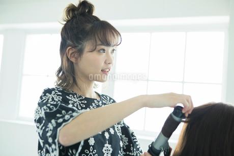 女性の髪の毛をスタイリングする女性美容師の写真素材 [FYI01737472]