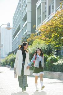 街を歩く笑顔の親子の写真素材 [FYI01737527]