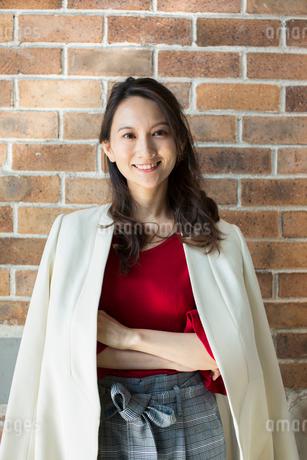 レンガの壁の前に立つ笑顔の30代女性の写真素材 [FYI01737528]