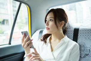タクシー車内でスマホを操作する20代女性の写真素材 [FYI01737554]