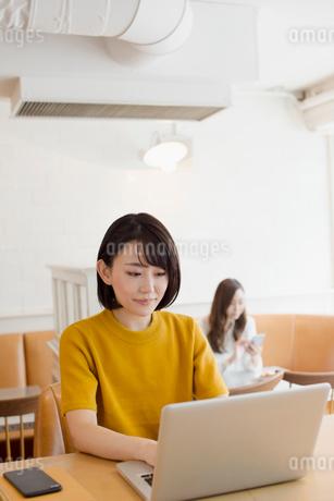 カフェでパソコンを操作する20代女性の写真素材 [FYI01737560]