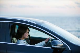 海沿いを運転する30代女性の写真素材 [FYI01737562]