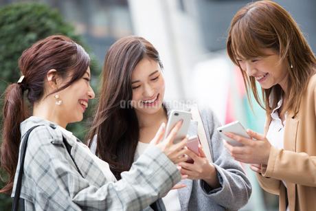 街でスマホを確認する20代女性3人の写真素材 [FYI01737572]
