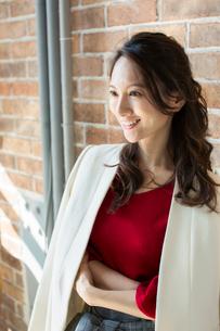 レンガの壁の前に立つ笑顔の30代女性の写真素材 [FYI01737578]
