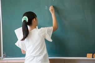 黒板に板書する女の子の写真素材 [FYI01737603]