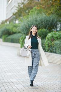 ビル街を歩く笑顔の30代女性の写真素材 [FYI01737626]