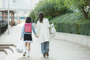 買い物帰りの親子の後ろ姿の写真素材 [FYI01737630]