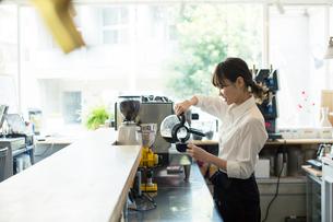 コーヒーを注ぐ20代カフェ店員の写真素材 [FYI01737637]