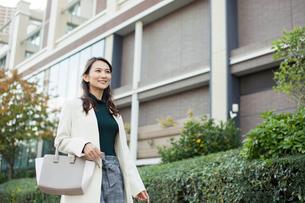ビル街を歩く笑顔の30代女性の写真素材 [FYI01737662]