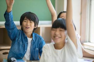 挙手をする笑顔の小学生達の写真素材 [FYI01737665]