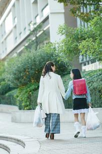 買い物帰りの親子の後ろ姿の写真素材 [FYI01737669]