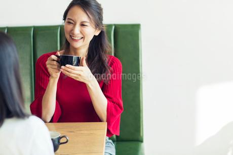 カフェで会話をする笑顔の30代女性の写真素材 [FYI01737694]