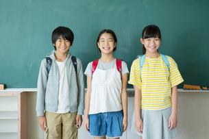 黒板の前に立つ小学生男女3人の写真素材 [FYI01737699]