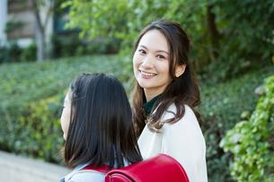 小学生と歩く笑顔の30代女性の写真素材 [FYI01737720]