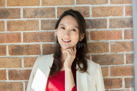 レンガの壁の前に立つ笑顔の30代女性の写真素材 [FYI01737738]
