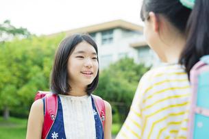 笑顔で会話をする小学生女子2人の写真素材 [FYI01737743]