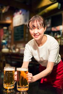 ビールを運ぶ笑顔の居酒屋店員の写真素材 [FYI01737745]