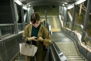 エスカレーターに乗る20代女性の写真素材 [FYI01737749]