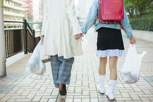 買い物帰りの親子の後ろ姿の写真素材 [FYI01737756]