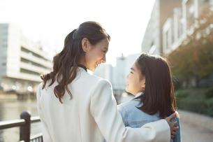 街を歩く笑顔の親子の写真素材 [FYI01737772]