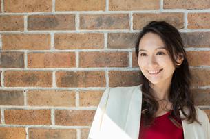 レンガの壁の前に立つ笑顔の30代女性の写真素材 [FYI01737782]